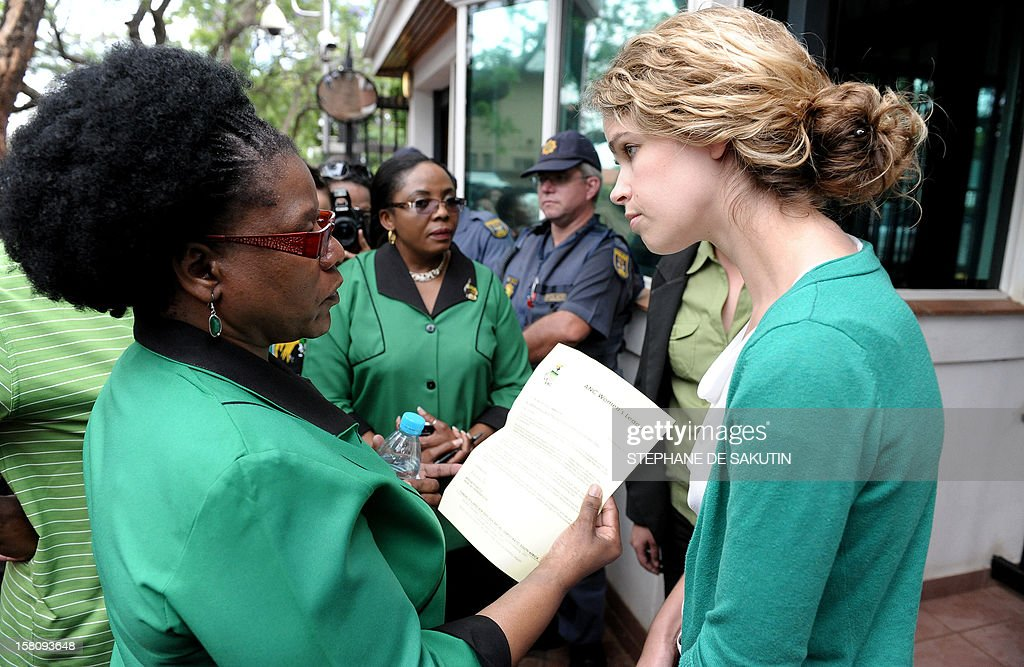 A member of the African National Congress (ANC) Women's league hands over a letter to a representative (R) of the British High Commission on December 10, 2012 front of the British High Commission in Pretoria to demand Shrien Dewani be extradited back to South Africa and stand trial for the crimeof which he is accused. Dewani is fighting against being extradited from the UK to South Africa, allegedly for masterminding his wife's murder on November 13, 2011 in a poor township on the outskirts of Cape Town. Dewani's extradition hearing will begin again in July in Britain. AFP PHOTO / STEPHANE DE SAKUTIN