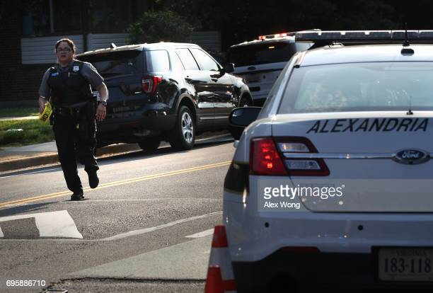 A member of the Alexandria Police runs up the street near the scene of an opened fire June 14 2017 in Alexandria Virginia Multiple injuries were...