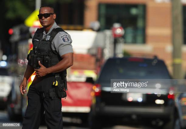 A member of the Alexandria Police stands guard near the scene of an opened fire June 14 2017 in Alexandria Virginia Multiple injuries were reported...