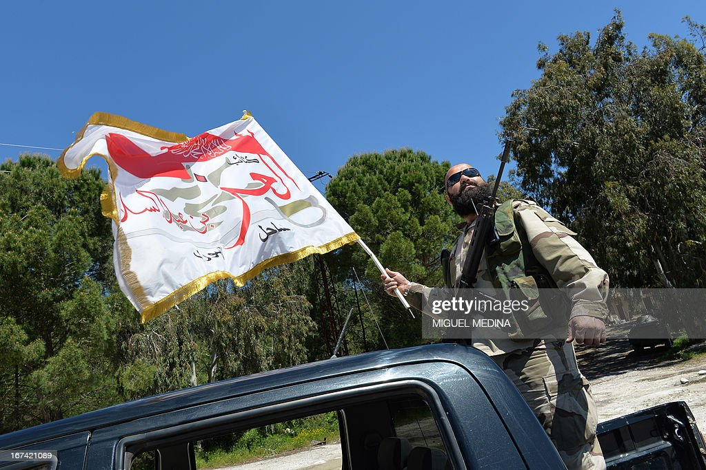 A member of the Al-Ezz bin Abdul Salam brigade waves a flag of the Katiba on the back of a pick-up truck before a training session at an undisclosed location near the al-Turkman mountains, in Syria's northern Latakia province, on April 25, 2013. AFP PHOTO / MIGUEL