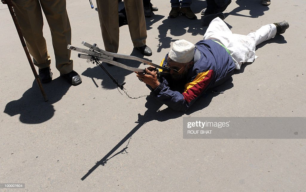 A member of the All Jammu and Kashmir Handicapped Association (AJKHA) lies on the ground holding a metal object representing a gun after Indian police detained some members during a protest in Srinagar on May 20,2010. The All Jammu and Kashmir Handicapped Association (AJKHA) were demanding an increase in monthly pensions and free education for deaf and blind handicapped people . AFP PHOTO/Rouf BHAT