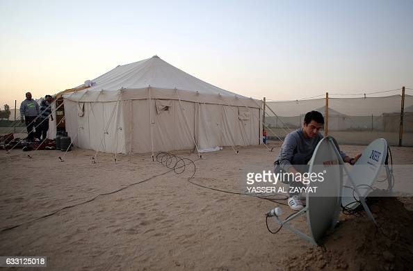 A member of the alShammari family fixes a satellite dish outside a tent in a winter camp close to the border with Saudi Arabia in alJulaia around 70...
