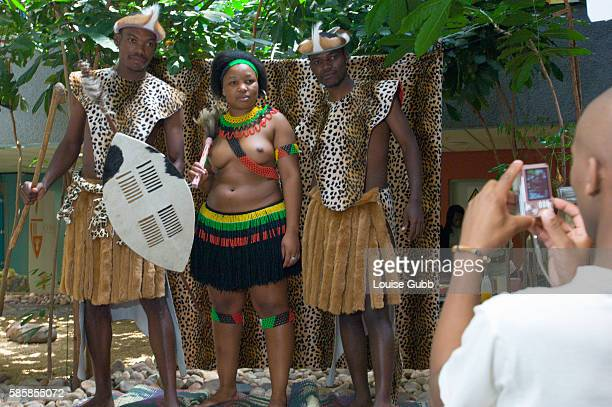 A member of the 'Amasiko Esintu Upholdings' group photographs students with a cell phone against a makeshift backdrop with hired Zulu traditional...