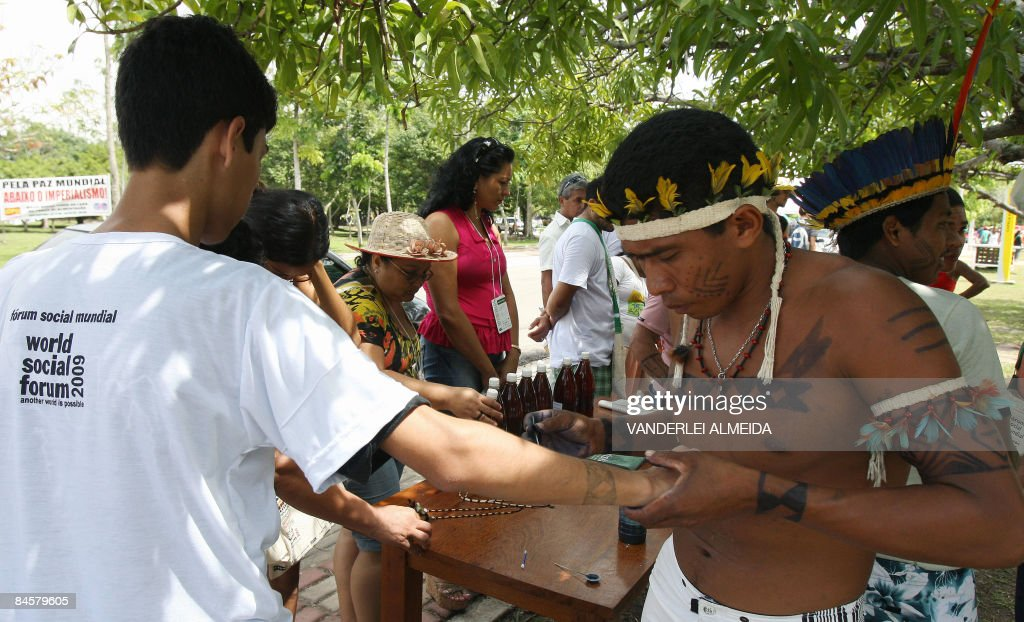 A member of the Amazonian Tembe tribe makes a tattoo on the arm of a participant of the World Social Forum on the camping grounds of the Federal...