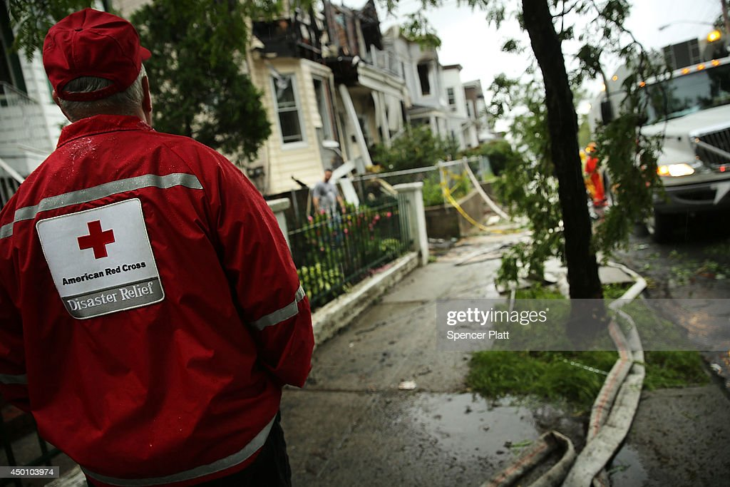 A member of the American Red Cross looks on as firefighters work at the scene of a fivealarm fire that burned for several hours on June 5 2014 in the...