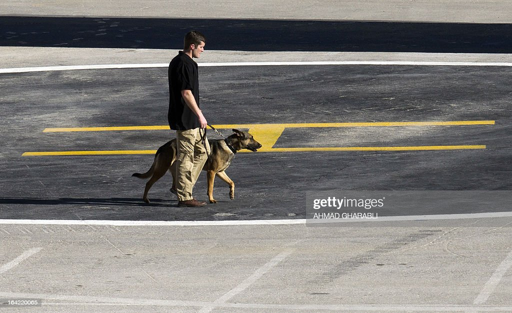 A member of the American security team walks with a dog while checking the premises of the helipad where US President Barack Obama is supposed to land later in the day at the Palestinian Authority Headquarters in the West Bank city of Ramallah on March 21, 2013. Obama is traveling to the West Bank to meet Palestinian leaders dismayed by his failure to meet expectations that he could help deliver them a state.