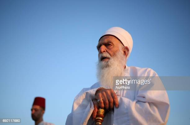A member of the ancient Samaritan community prays as he prepares to take part in the traditional pilgrimage marking the holiday of Shavuot atop Mount...