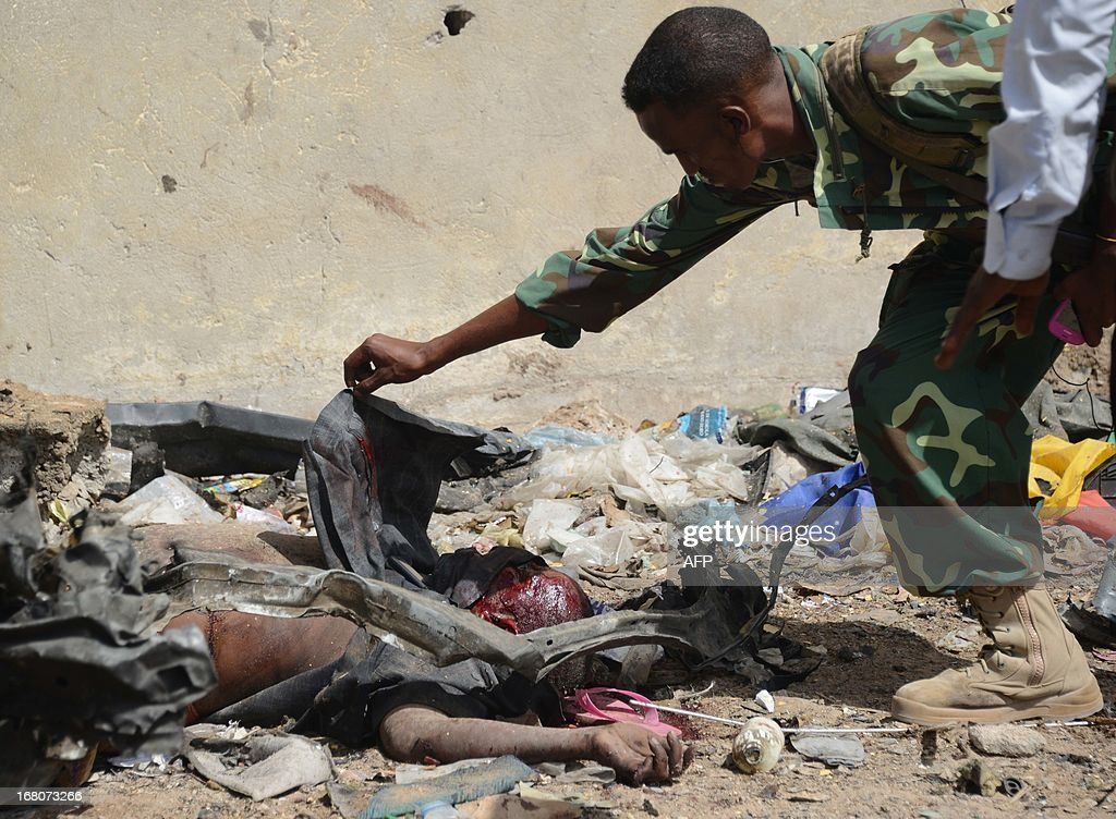A member of the army looks at a victim of the suicide bombing following a suicide attack on a government convoy in Mogadishu on May 5, 2013. Around 11 people were killed today when a suicide attacker rammed a car laden with explosives into a government convoy at a busy junction in the Somali capital, police said.