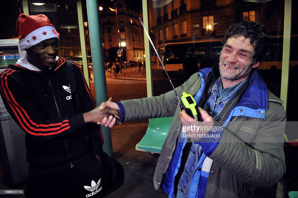 A member (L) of the Association 'Les Enfants du Canal' distributes a radio to a homeless man, in a street in Paris, on December 21, 2012. Thousands of radios will be distributed to the homeless in the streets of Paris from December 21 to 24 to 'break their isolation' and give them access to information and culture. This initiative named '1000 radios' is funded 70% by the non-profit 'Fondation de France', as part of its project 'Christmas Eves of Solidarity'.
