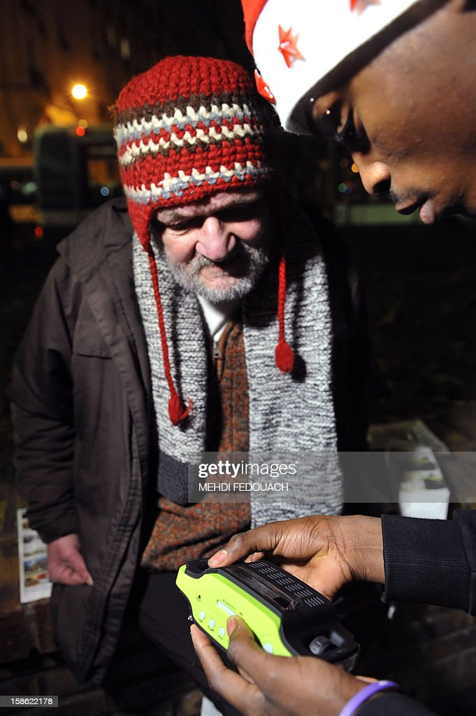 A member (R) of the Association 'Les Enfants du Canal' distributes a radio to a homeless man, in a street in Paris, on December 21, 2012. Thousands of radios will be distributed to the homeless in the streets of Paris from December 21 to 24 to 'break their isolation' and give them access to information and culture. This initiative named '1000 radios' is funded 70% by the non-profit 'Fondation de France', as part of its project 'Christmas Eves of Solidarity'.