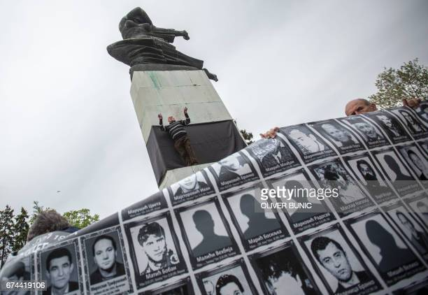 A member of the Association of Families of Kidnapped and Murdered in Kosovo stands in front of the monument of Gratitude to France which message...