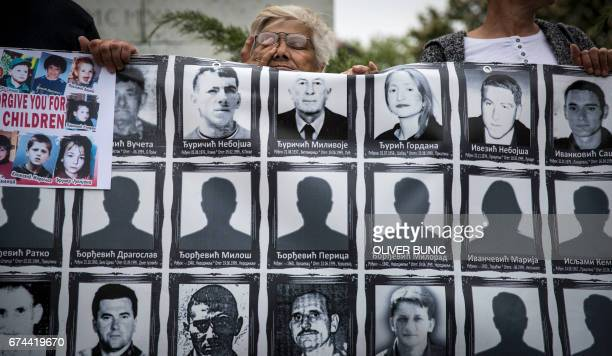 A member of the Association of Families of Kidnapped and Murdered in Kosovo gestures as she holds a banner depicting missing and killed relatives...