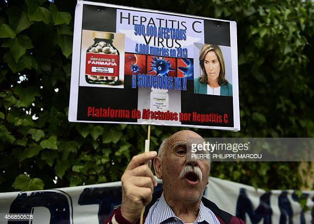 A member of the associations for Hepatitis C victims holds a banner during a protest outside the Carlos III hospital in Madrid on October 8 2014...