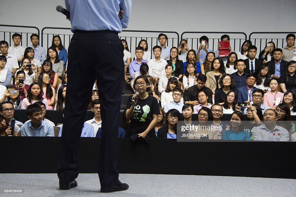 A member of the audience asks US President Barack Obama (in foreground) a question as he speaks at the Young Southeast Asian Leaders Initiative town hall event in Ho Chi Minh City on May 25, 2016. Obama urged communist Vietnam on May 24 to abandon authoritarianism, saying basic human rights would not jeopardise its stability, after Hanoi barred several dissidents from meeting the US leader. / AFP / JIM