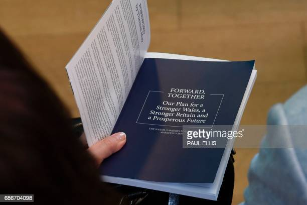 A member of the audience holds a copy of the Conservative Party general election manifesto during a launch event for the Welsh Conservative general...