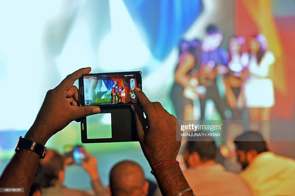 A member of the audience records a video on his mobile phone as Indian models showcase the new Samsung 'Galaxy S5', smartphone during a fashion show held as part of a consumer event in Bangalore on April 10, 2014. The phone along with its wearable 'Gear 2' will be available on sale across India from April 11, works on a firstime, True OctaCore Proccesor. AFP PHOTO/Manjunath KIRAN