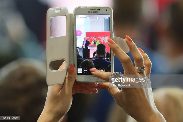 A member of the audience takes a photo on a mobile phone as leader of the Labour Party Jeremy Corbyn and Shadow Education Secretary Angela Rayner...