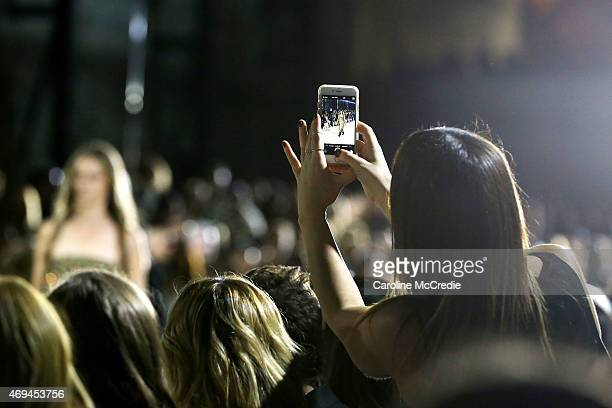 A member of the audience takes a photo on her smartphone at the MercedesBenz Presents Ellery show at MercedesBenz Fashion Week Australia 2015 at...