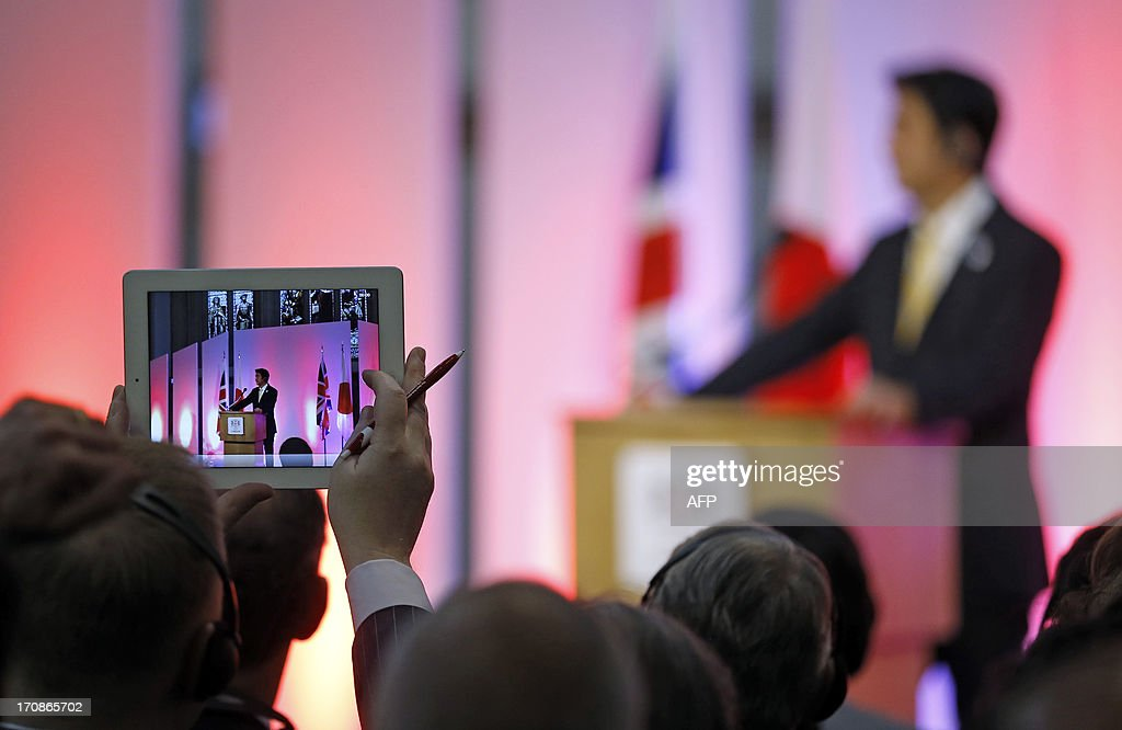 A member of the audience takes a picture with a tablet computer as Japan's Prime Minister Shinzo Abe gives a speech during a question and answer session at the Guildhall in London on June 19, 2013. AP