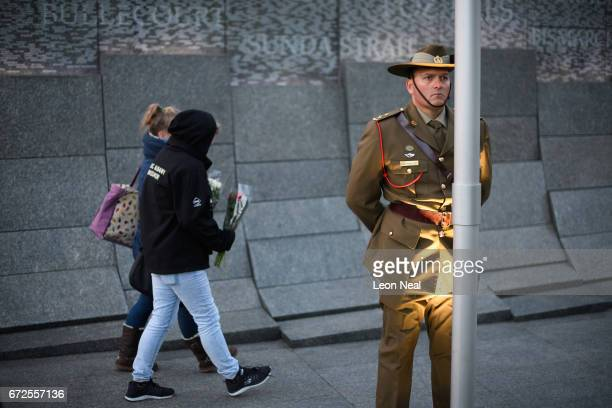 A member of the Australian armed forces stands to attention as people lay wreaths and floral tributes at the Australian War Memorial at Hyde Park...