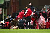 A member of the Australian Army Red Beret's receives attention after landing heavily on the SCG during the round five AFL match between the Sydney...