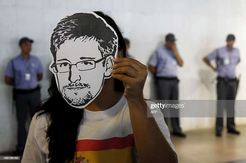 A member of the Avaaz online community organization wears a 'Snowden' mask during the delivery at the the Itamaraty Foreign Ministry Palace of signatures supporting the granting of political asylum by Brazilian President Dilma Rousseff to <a gi-track='captionPersonalityLinkClicked' href=/galleries/search?phrase=Edward+Snowden&family=editorial&specificpeople=10983676 ng-click='$event.stopPropagation()'>Edward Snowden</a>, in Brasilia, on February 13, 2014. Avaaz members have collected over a million signatures in favor of the asylum application for Snowden, the former CIA technician that disclosed the spying by the U.S. government to millions of people, among whom President Rousseff and German Chancellor Angela Merkel. AFP PHOTO/Beto BARATA
