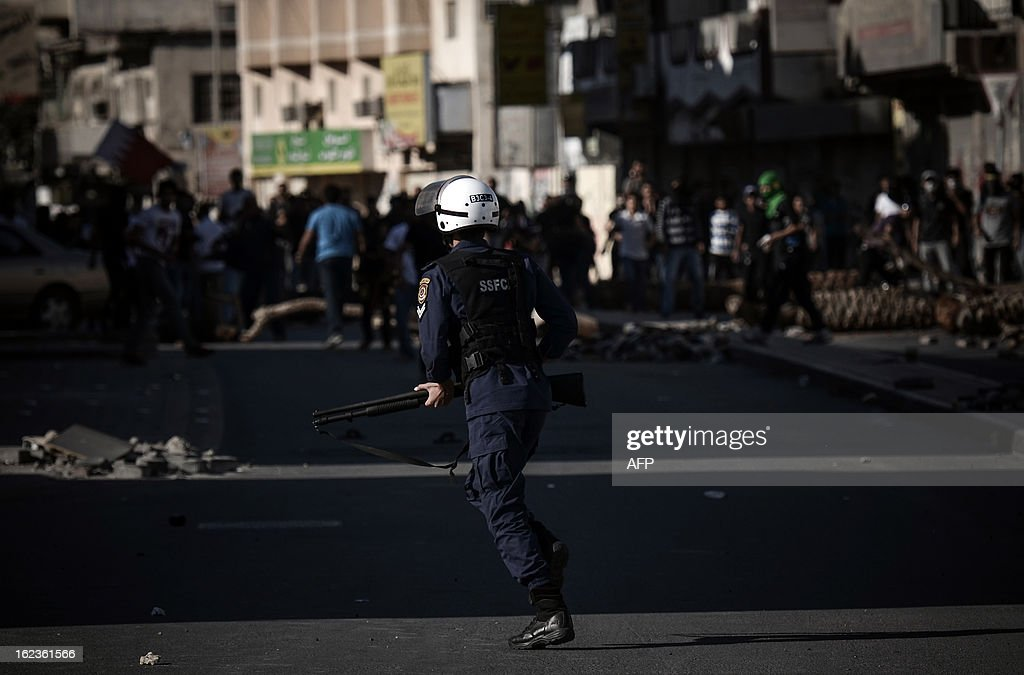 A member of the Bahraini riot police force tries to disperse anti-regime protestors during clashes following a demonstration against the killing of 20-year old Mahmud al-Jaziri, in the village of Daih, West of Manama, on February 22, 2013. The Shiite protester died of wounds after he was shot during clashes with Bahraini police on the second anniversary of the February 14, 2011 uprising.