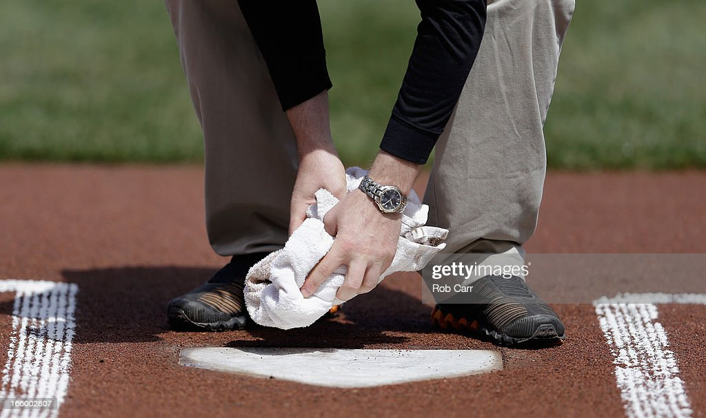 A member of the Baltimore Orioles grounds crew clean off home plate before the start of the Baltimore Orioles and Minnesota Twins game at Oriole Park at Camden Yards on April 7, 2013 in Baltimore, Maryland.