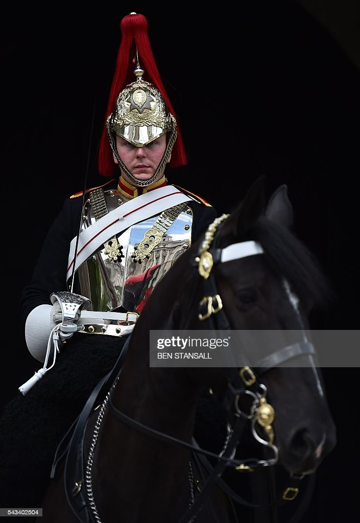 A member of the Blues and Royals, one of the squadrons that form the Household Cavalry Mounted Regiment, sits upon his horse as they stand guard on Whitehall in central London on June 28, 2016. EU leaders attempted to rescue the European project and Prime Minister David Cameron sought to calm fears over Britain's vote to leave the bloc as ratings agencies downgraded the country. Britain has been pitched into uncertainty by the June 23 referendum result, with Cameron announcing his resignation, the economy facing a string of shocks and Scotland making a fresh threat to break away. / AFP / BEN
