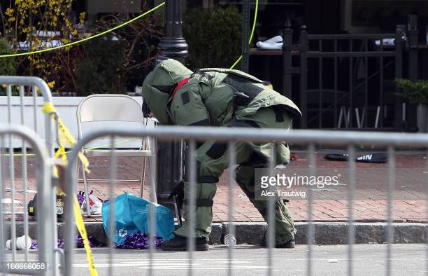 A member of the bomb squad investigates a suspicious item on the road near Kenmore Square after two bombs exploded during the 117th Boston Marathon...