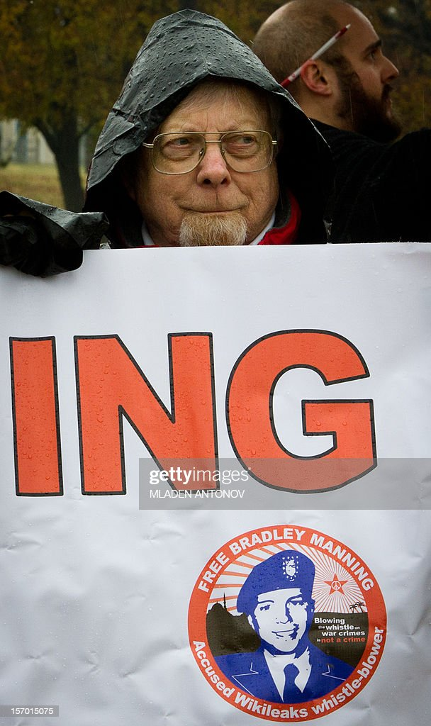 A member of the Bradley Manning Support Group holds a banner during a rally at the entrance of Fort George G. Meade military base in Fort Meade, Maryland on November 27, 2012. Manning is accused of downloading 260,000 US diplomatic cables, videos of US air strikes and US military reports from Afghanistan and Iraq between November 2009 and May 2010 and turning them over to WikiLeaks in what has been called one of the most serious intelligence breaches in US history. AFP PHOTO/ MLADEN ANTONOV