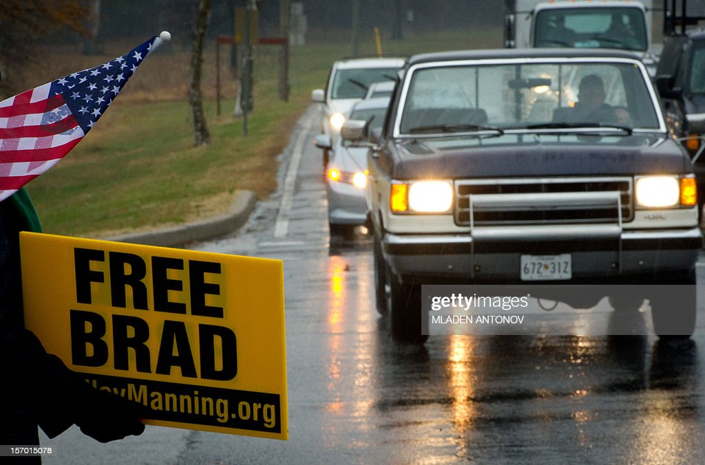 A member of the Bradley Manning Support Group holds a banner during a rally at the entrance of Fort George G. Meade military base in Fort Meade, Maryland on November 27, 2012. Manning is accused of downloading 260,000 US diplomatic cables, videos of US air strikes and US military reports from Afghanistan and Iraq between November 2009 and May 2010 and turning them over to WikiLeaks in what has been called one of the most serious intelligence breaches in US history.