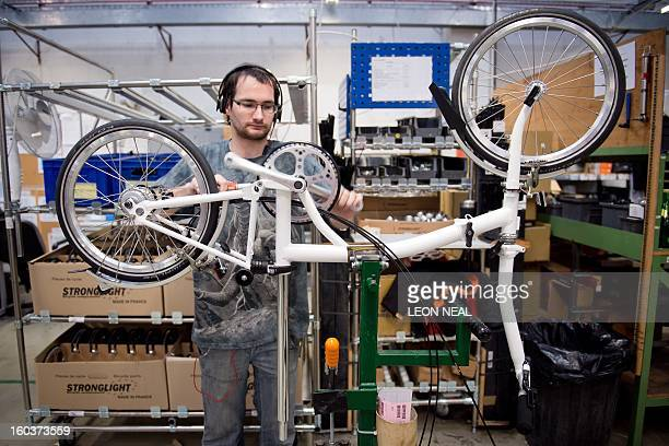 A member of the Brompton Bikes manufacturing team assembles the drive chain system of a folding bicycle on the production line at the company's...