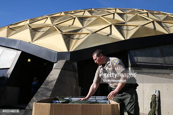 A member of the Butte County Sherriff's Department folds cots at an emergency shelter after a mandatory evacuation order in place since Sunday was...