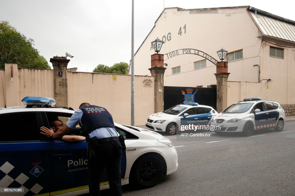 A member of the Catalan autonomous police force known as Mossos d'Esquadra (2nd-L) speaks with a local police officer outside the Santa Eulalia Spanish military base in Sant Boi near Barcelona on October 4, 2017. Catalonia could declare independence on October 9, a regional government source told AFP, as a crisis escalates between Madrid and separatist leaders over an illegal independence referendum. /