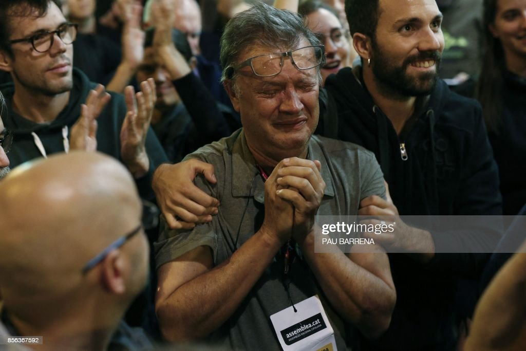 TOPSHOT - A member of the Catalan National Assembly (ANC) cries at the end of the voting day at the 'Espai Jove La Fontana' (La Fontana youth center) polling station, on October 1, 2017 in Barcelona. Spanish riot police stormed voting stations today as they moved to stop Catalonia's independence referendum after it was banned by the central government in Madrid. At least 92 people were confirmed injured as hundreds tried to prevent the polling stations from being closed, Catalan officials said. A total of 465 people were treated at hospitals and health centres, while Spain's interior ministry said 12 police officers were injured. BARRENA