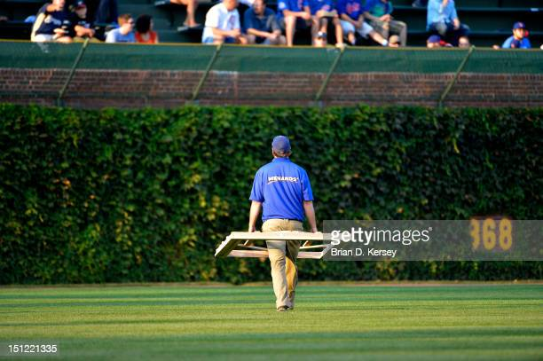 A member of the Chicago Cubs grounds crew takes the template for the batters' box out to center field before the game against the Milwaukee Brewers...