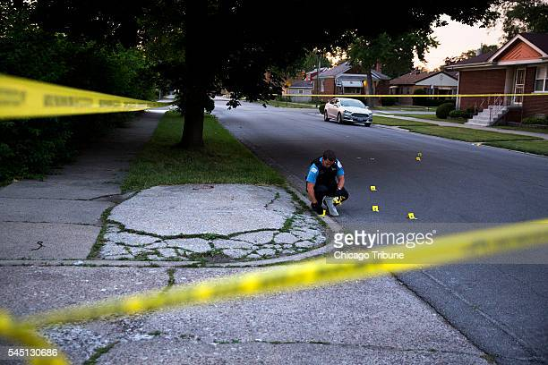 A member of the Chicago Police Department collects bullet casings at the scene of a shooting near the intersection of South Morgan Street and West...