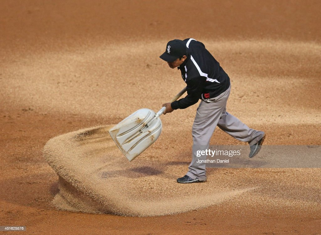 A member of the Chicago White Sox ground crew spreads drying agent onto the infield as the White Sox take on the Los Angeles Angels of Anaheim in a steady light rain at U.S. Cellular Field on July 2, 2014 in Chicago, Illinois.