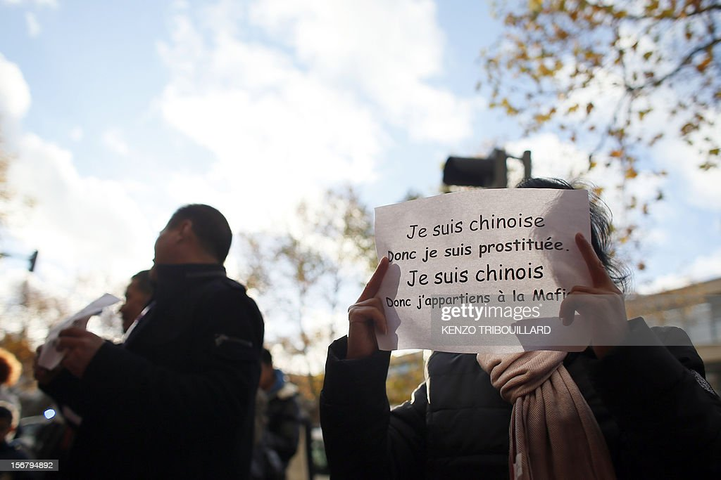 A member of the Chinese community in France holds a placard during a demonstration against xenophobia called by the association 'Francais de Chine, Chinois de France' (French from China, Chinese of France) on November 21, 2012 near the French newspaper Le Parisien's headquarters in Saint-Ouen, a northern suburb of Paris. Demonstrators denounce the stereotypes their community is subjected to after Le Parisien published on November 11 a special issue on the Chinese mafia in France. Placard reads : 'I am a Chinese woman, so I am a prostitute, I am a Chinese man, so I belong to the Mafia'.