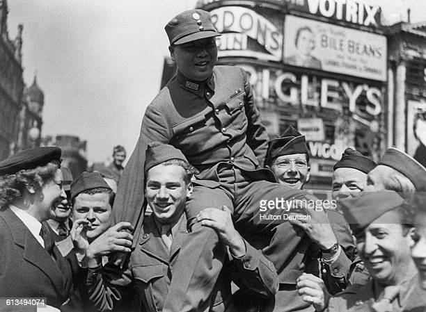 A member of the Chinese Military Mission in London is carried aloft on the shoulders of jubilant young servicemen celebrating news of Japan's...