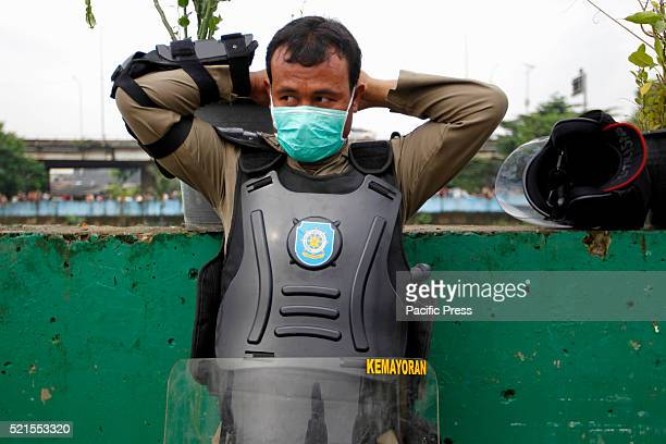 A member of the civil service police unit members puts on a protection mask during the demolition of Kalijodo redlight district Bulldozers started...