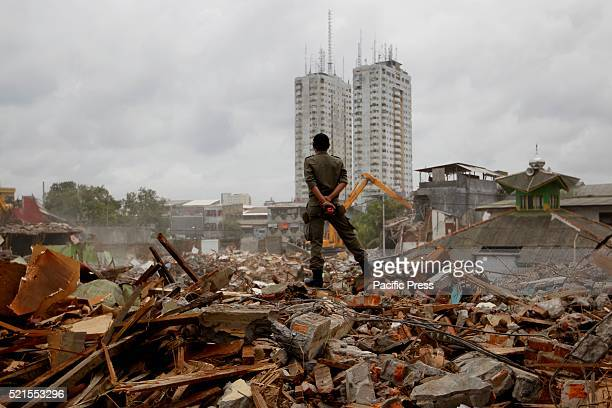 A member of the civil service police unit members stand as bulldozers demolish buildings at Kalijodo redlight distric Bulldozers started demolishing...