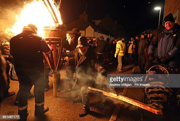 A member of the Clavie Crew hands a piece of the burning Clavie to a member of the public as they parade it through the streets of Burghead in Moray...