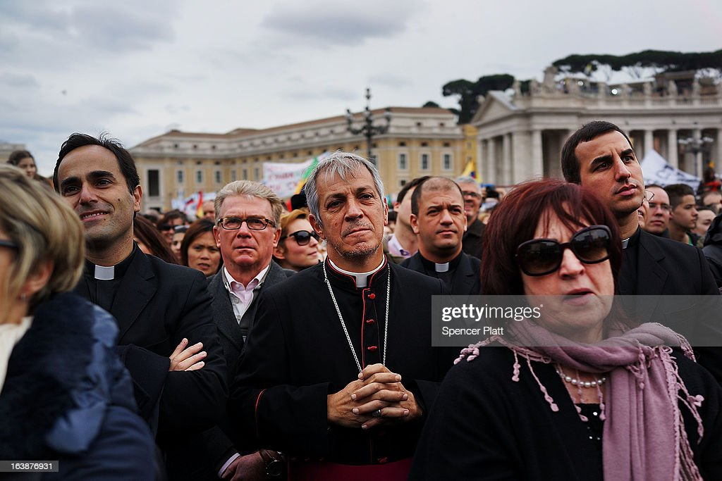 Member of the clergy and laypeople watch as Pope Francis appears in the window of his private residence in St Peter's Square to give his first Angelus blessing on March 17, 2013 in Vatican City, Vatican. The Vatican is preparing for the inauguration of Pope Francis on March 19, 2013 in St Peter's Square.