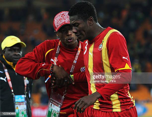 A member of the coaching staff tries to console Asamoah Gyan of Ghana after they lose the penalty shoot out and are out of the tournament during the...