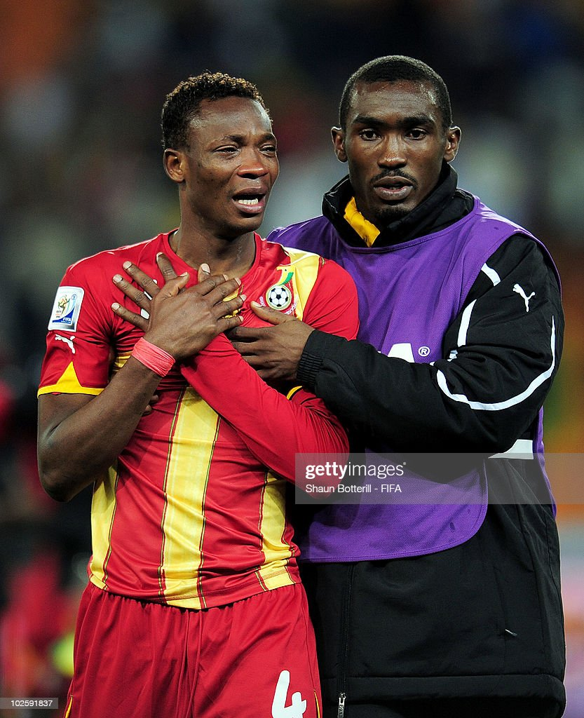 A member of the coaching staff tries to console John Pantsil of Ghana after they lose the penalty shoot out and are out of the tournament during the 2010 FIFA World Cup South Africa Quarter Final match between Uruguay and Ghana at the Soccer City stadium on July 2, 2010 in Johannesburg, South Africa.