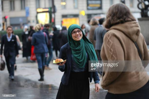 A member of the Collective against Islamophobia in France distributes French pastries called 'pain au chocolat' in front of the SaintLazare railway...