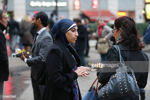 A member of the Collective against Islamophobia in France talks to a woman after giving her French pastries called 'pain au chocolat' in front of the...