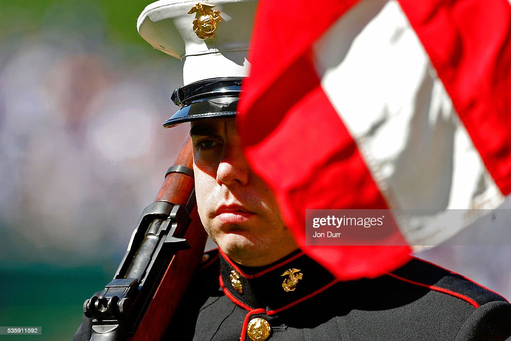 A member of the color guard's face is obscured by the American flag as the colors are presented before the singing of the national anthem before the game between the Chicago Cubs and the Los Angeles Dodgers at Wrigley Field on May 30, 2016 in Chicago, Illinois.